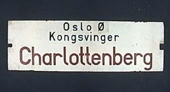 """Dubbelsidig vändbar plåtskylt med svart och röd text på vit botten. På ena sidan står det: """"Charlottenberg Kongsvinger Oslo Ø""""  På andra sidan: """"Oslo Ø Kongsvinger Charlottenberg"""""""