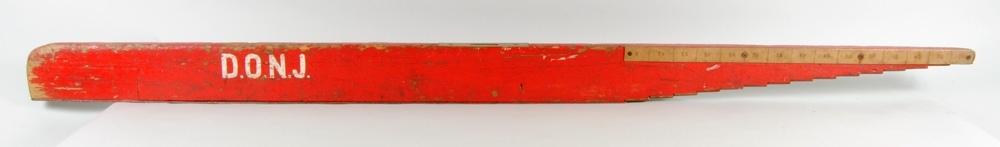 """Rälsförhöjningsmått, rödmålat. Skrivet med schablon """"D.O.N.J."""". Högra delen är utformad som en omvänd trappa och ovanför respektive steg står ett millimetermått mellan 5-75. Måttet anger höjdskillnaden."""