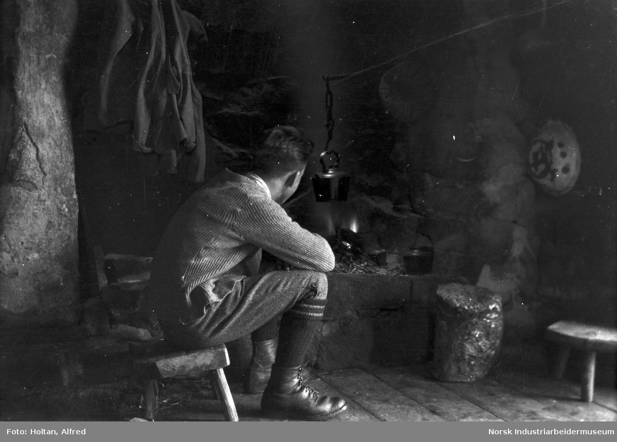 Ung mann ved åpent ildsted.