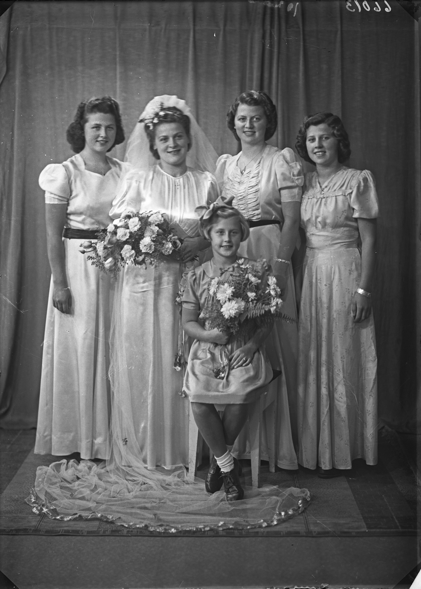 Brudebilde. Familiegruppe på fem. Fire unge kvinner, den ene brud, og en ung pike. Søstre. Brudgruppe. Bestilt av Herr Lauritz Hovland