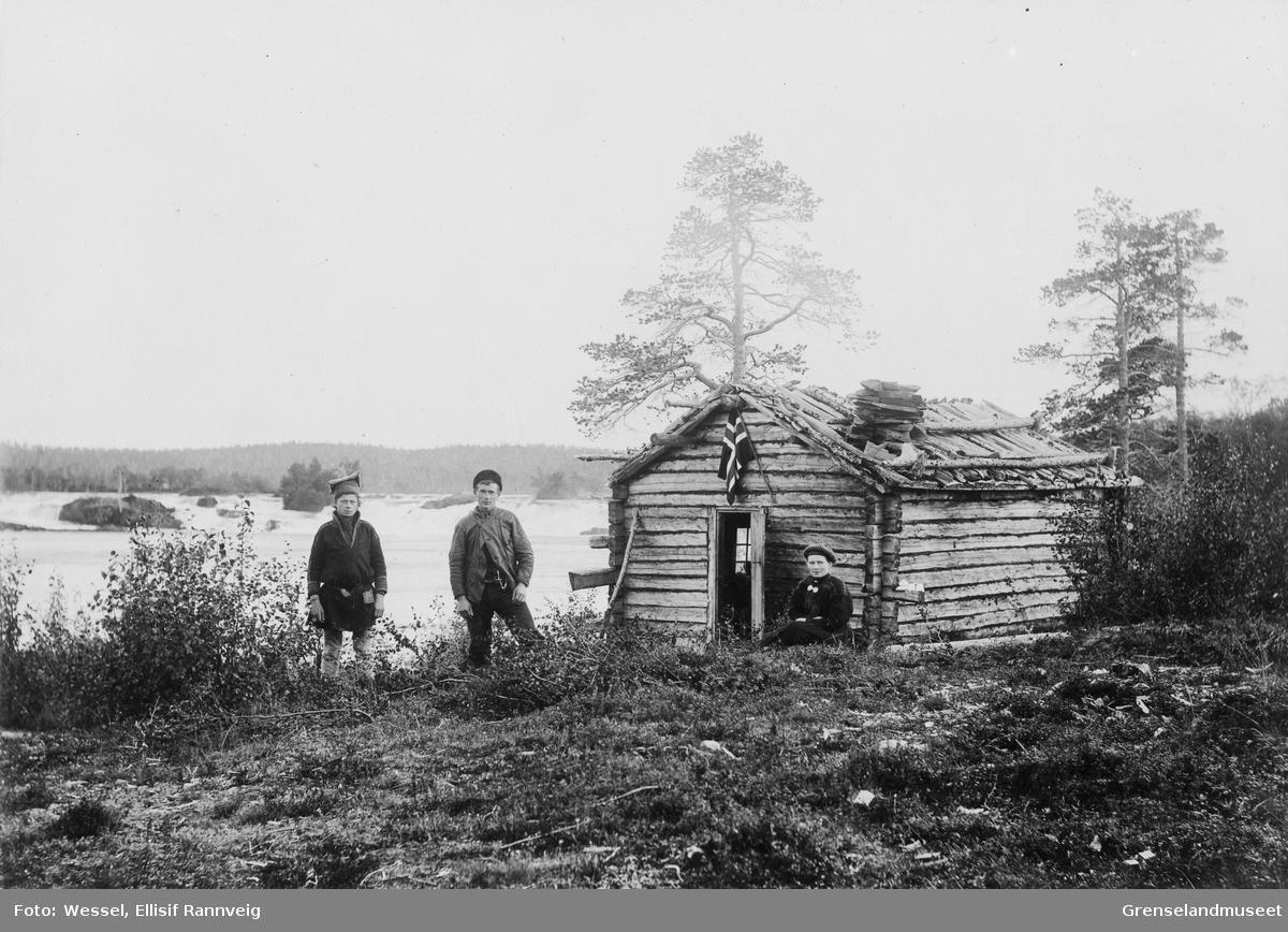 Ved Männikäkoia/Skogfosskoia 1896. Frk. Lilleng sitter ved døra. Ole Johnsen Must og Oskar Beddari er med som skysskarer.
