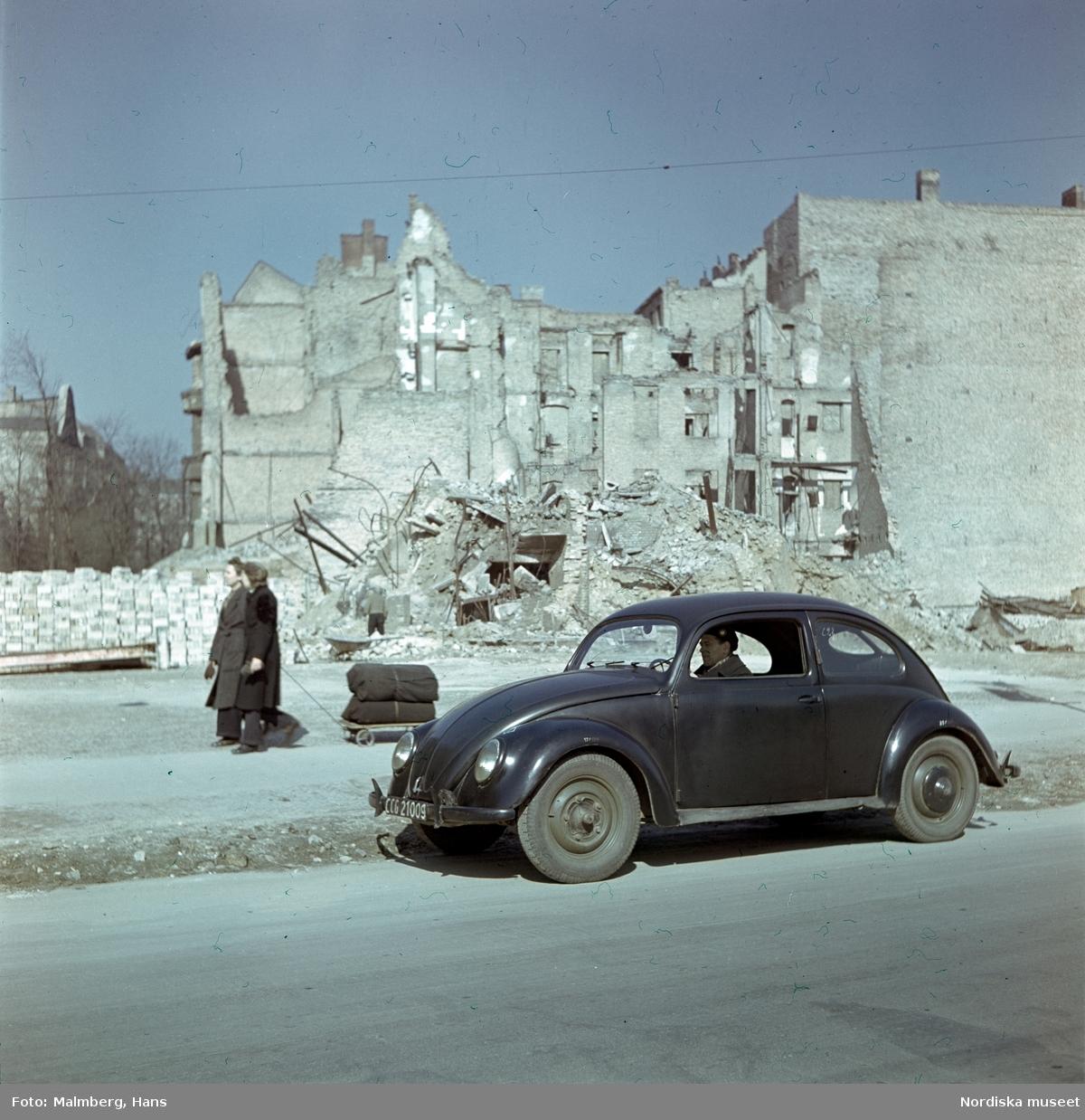 Berlin. En soldat ur de brittiska ockupationstrupperna kör en Volkswagen. I bakgrunden husruiner och två kvinnor med en kärra.