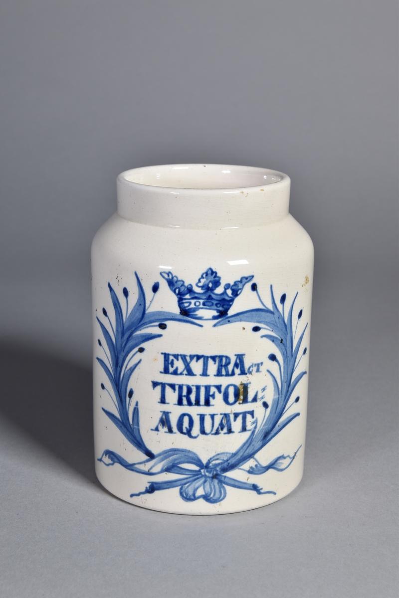 Apoteksburk av vitglaserat flintgods, cylindrisk. Blå text inskriven i lagerbladskrans med krona. Sekundär pappersetikett.