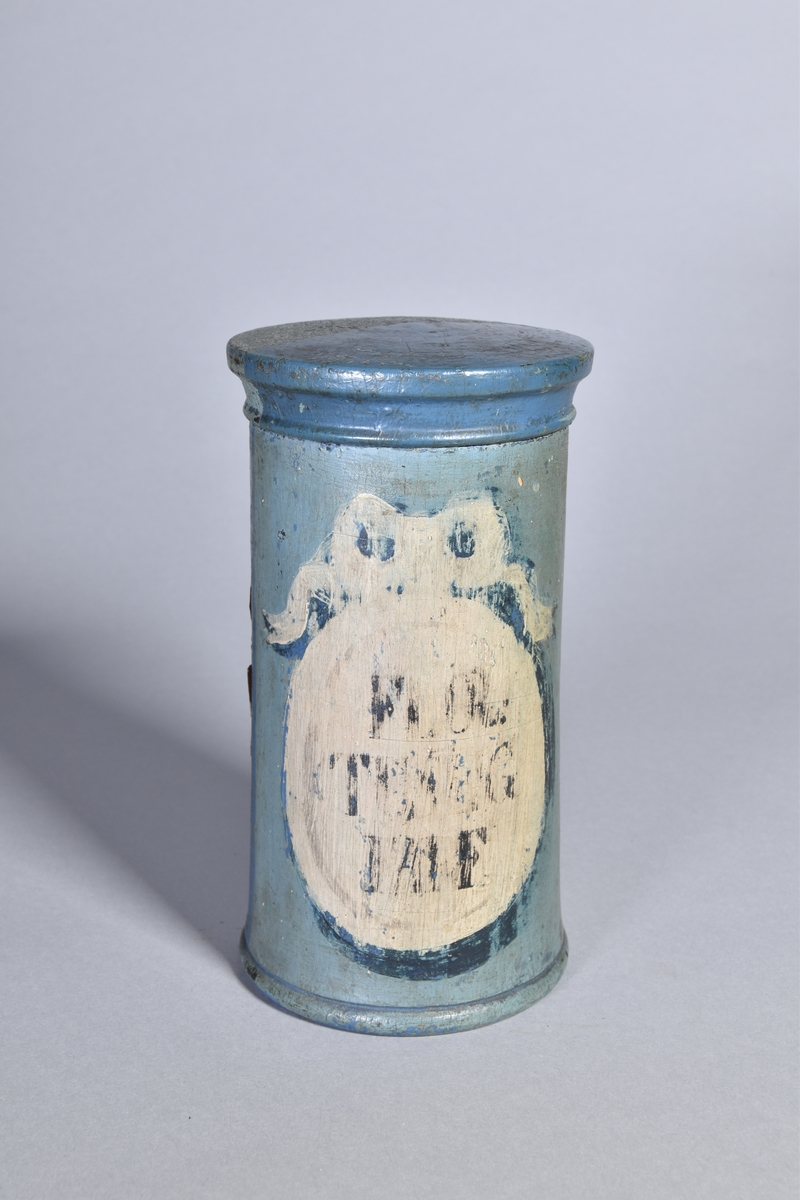 Ståndkärl av grönmålat trä, cylindriskt med plant lock. Svart text inom oval med bandrosett. Oläslig påskrift. Baksidan blåmålad med sekundär etikett.