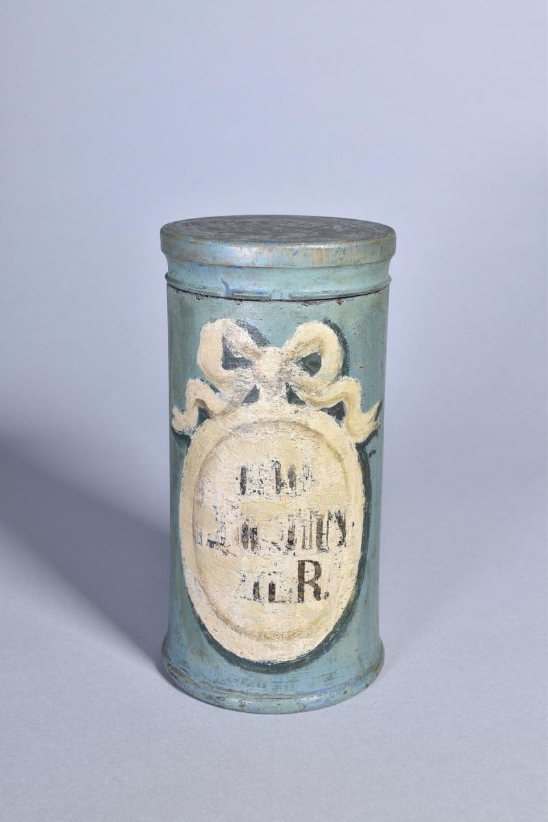 Apotekskärl, ståndkärl, av grönmålat trä, cylindriskt med plant lock. Svart text inom oval med bandrosett. Oläslig påskrift.