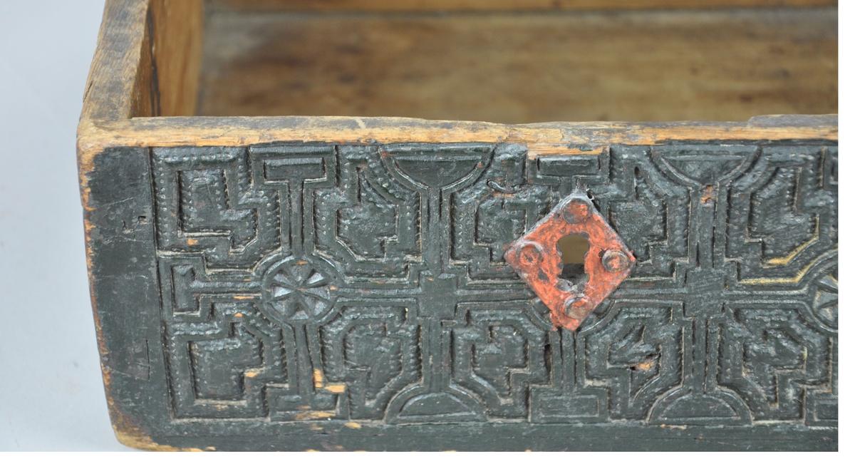 Eske av tre, med manglende lokk. Esken er svartmalt og har karveskurd på utsiden av sideplatene. Det skjærte dekoret består av sirkler, kors og geometriske figurer. På midten av hver sideplate er det en rødmalt sirkel, og beslag til nøkkelhull er også malt rødt.   Gammelt katalogbilde viser esken med lokk, men dette lokket sitter altså ikke lenger på.