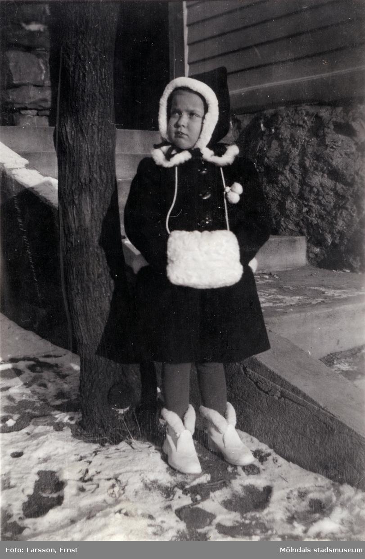 """Berit Gustafsson vinterklädd i muff och kappa en kall vinter i början av 1940-talet. Platsen är i """"Stusshålan"""", Kryssgatan i Mölndal."""