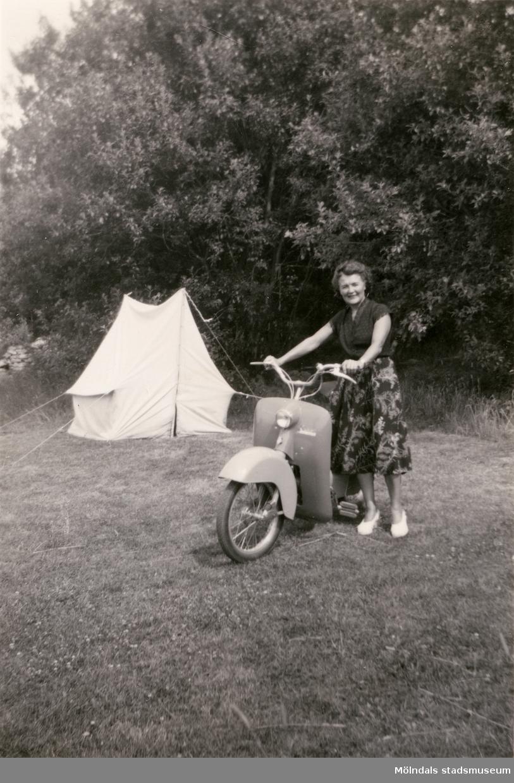 Karin Hasselberg står vid sin scooter, ett tält syns i bakgrunden. Ca 1940-1950-tal.