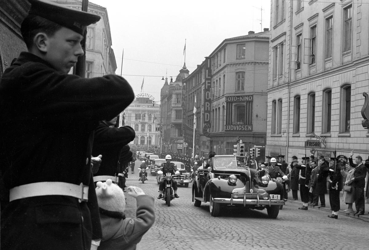 Finlands president Urho Kekkonen kommer på statsbesøk til Norge. Bilkortesjen med presidenten og Kong Olav i spissen på vei fra Østbanestasjonen til Slottet. Bilen med registreringsnummer A-1 er en Buick 1939 Roadmaster convertible Sedan. Bak ses en Cadillac.