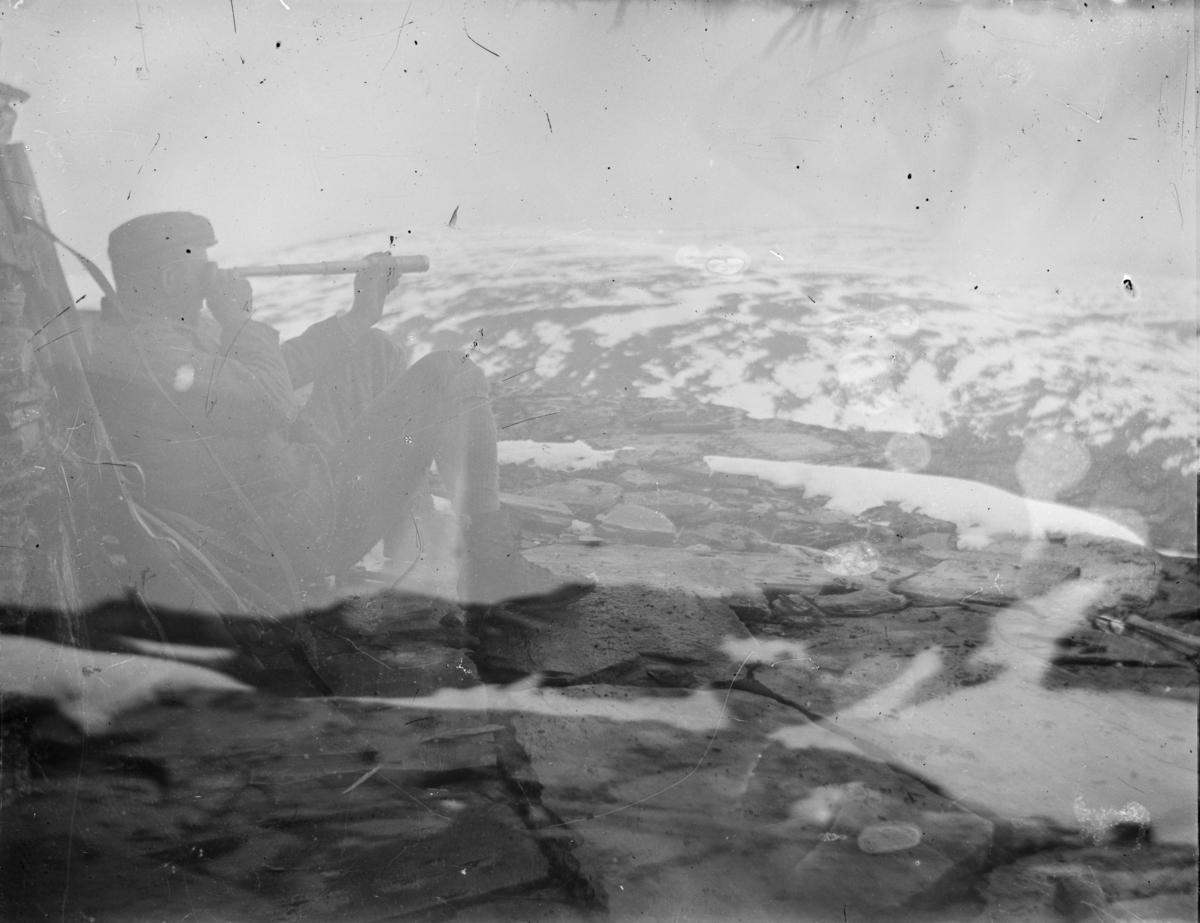 Mann sitter på fjelltopp med børse og ser i monokolar (kikkert)