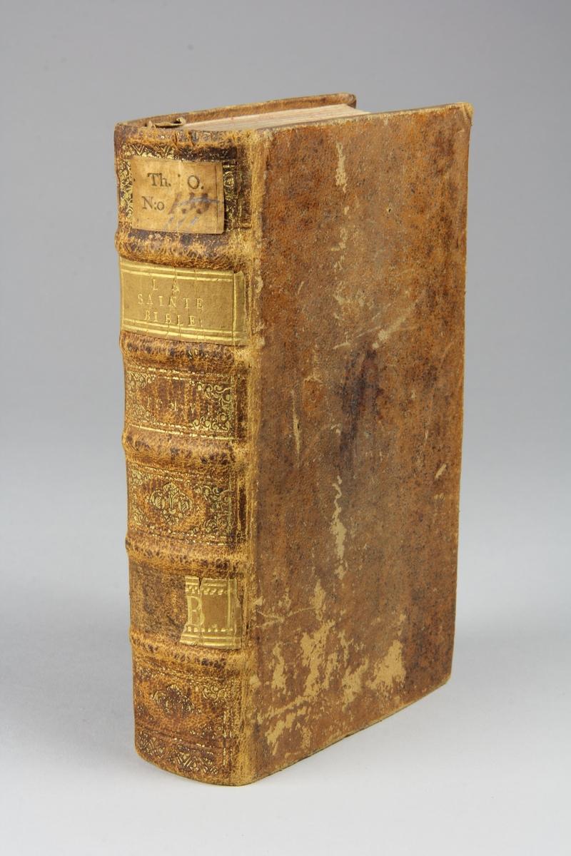 """Bok, helfranskt band """"La sainte bible traduite en françois sur la Vulgate"""", del 7. Skinnband med guldpräglad rygg i fem upphöjda bind, skuret rödstänkt snitt. Pärmarnas insidor klädda med marmorerat papper."""
