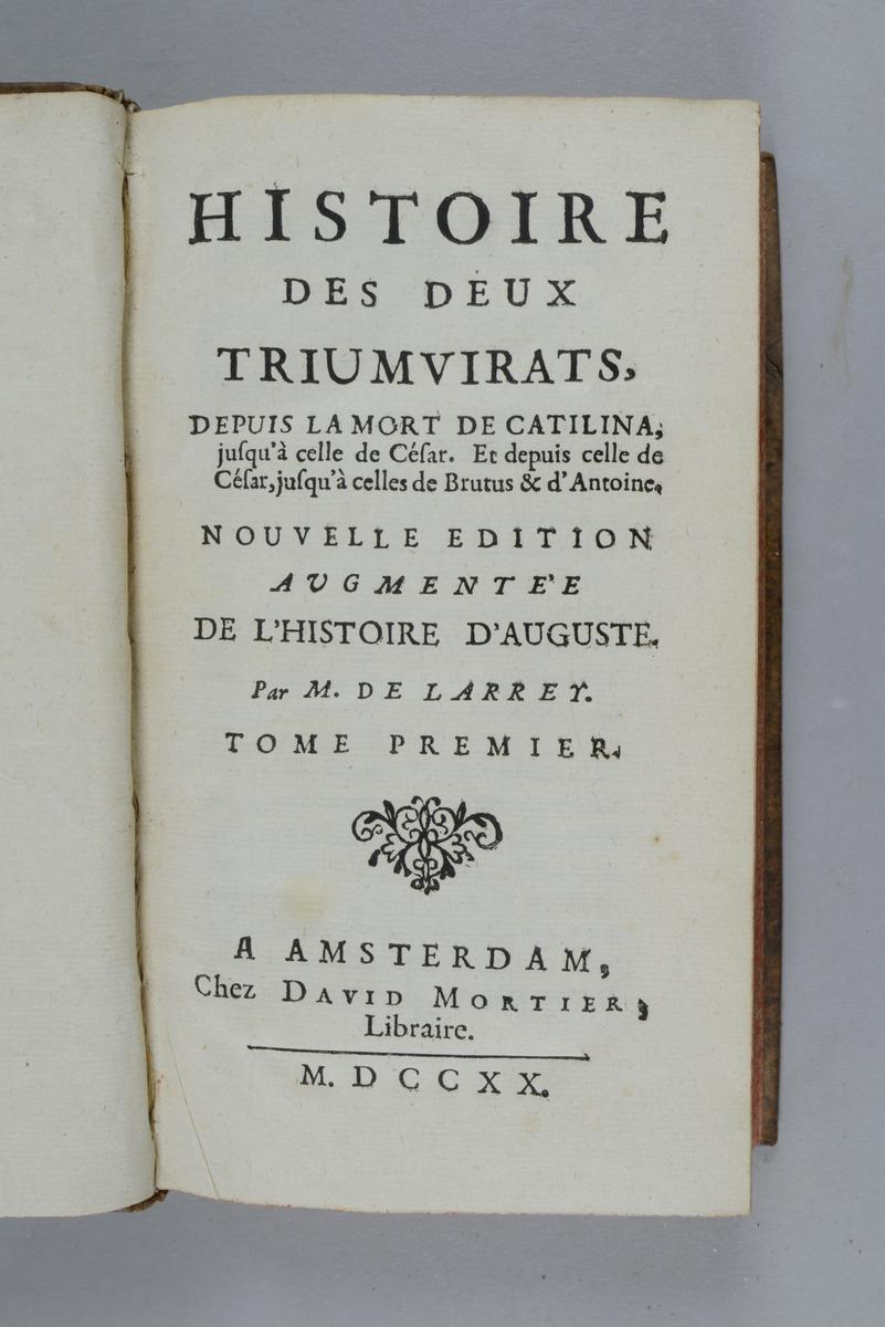 """Bok, helfranskt band """"Histoire des deux triumvirats"""" del 1, tryckt i Amsterdam 1720. Skinnband med blindpressad och guldornerad rygg i fem upphöjda bind, titelfält med blindpressad titel, fält med volymens nummer och påklistrad pappersetikett. Med rödstänkt snitt och marmorerat papper på pärmarnas insidor. Anteckning om inköp på försättsbladet."""