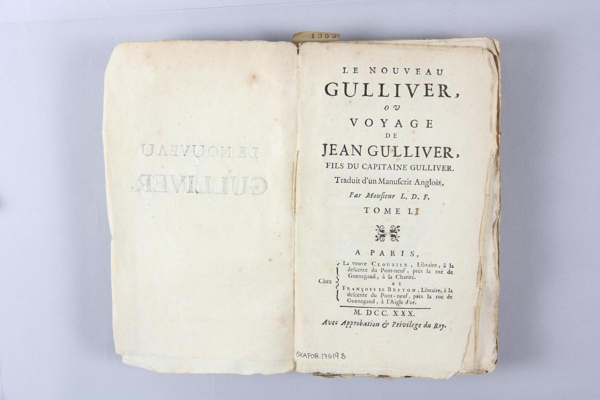 """Bok, häftad,""""Le Nouveau Gulliver ou Voyage de Jean Gulliver"""", del 2, tryckt 1730 i Paris. Pärm av marmorerat papper, oskuret snitt. Blekt rygg med pappersetikett med volymens namn, svårläst,  och samlingsnummer."""