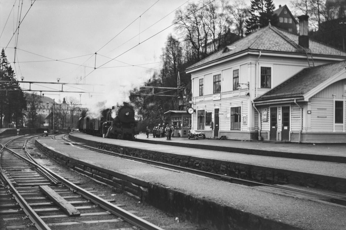 Godstog til Bergen, tog 5515, på Nesttun stasjon, forbikjøres av lokaltog til Bergen. Godsoget trekkes av damplokomotiv type 31b nr. 426. I lokaltoget motorvogn type Bmeo 65.