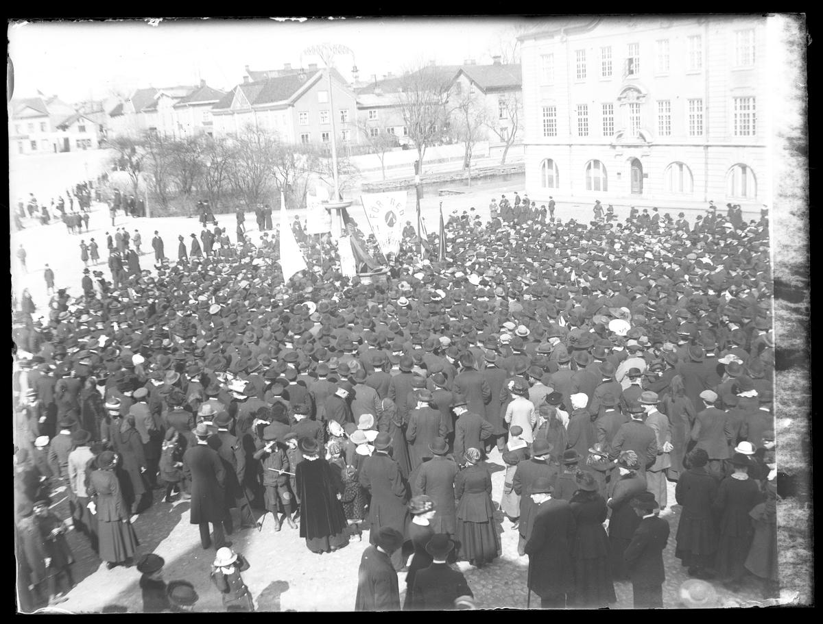 Första maj-demontration på Lilla torget. Kvinnor, män och barn i mörka kläder har samlats på torget och står vända mot Stora torget.