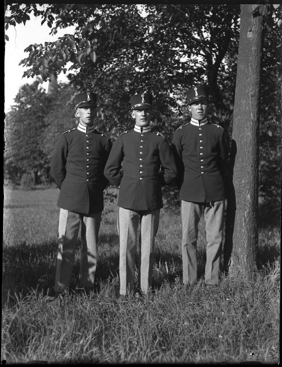 Tre män i militäruniform står bredvid ett träd. Bilden tagen under fotografen Harald Olssons excercistid.