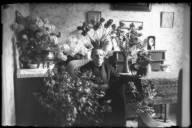 Fru Dahlgren sitter i en korgstol i ett finrum omgiven av blommor. Porträttet taget i samband med 60årsdagen.