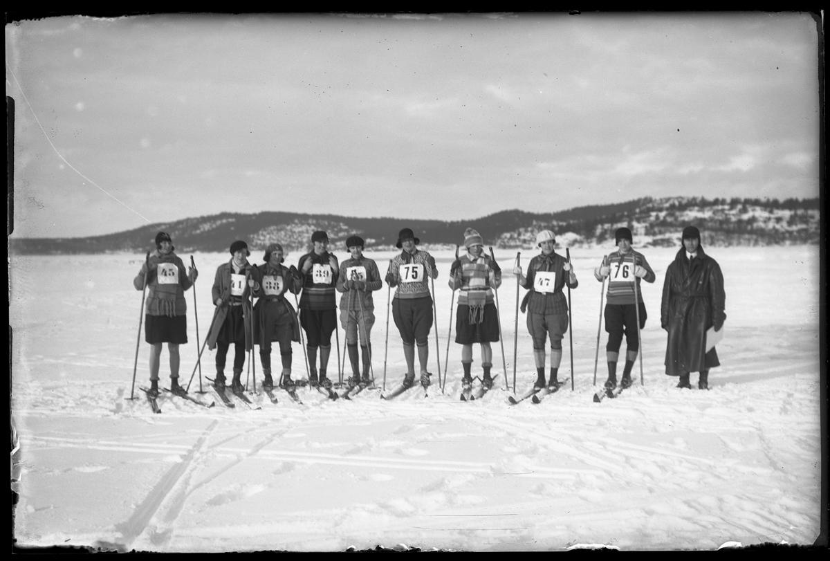 """En grupp med kvinnor på skidor står uppradade på en snötäckt is. I fotografens egna anteckningar står det """"Skidtävlingen Kvinnliga"""""""