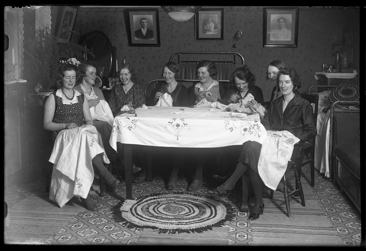 """8 glada kvinnor sitter runt ett bord och handarbetar. I fotografens anteckningar står det """"Symöte hos Gust. Johansson""""."""