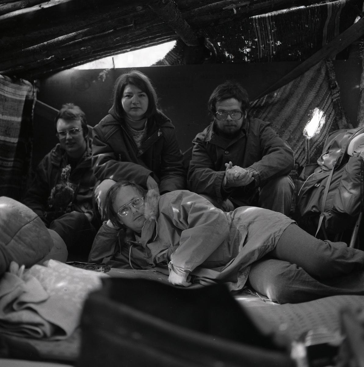 I en koja sitter tre personer mot väggen medan en fjärde ligger vid deras fötter, våren 1975.