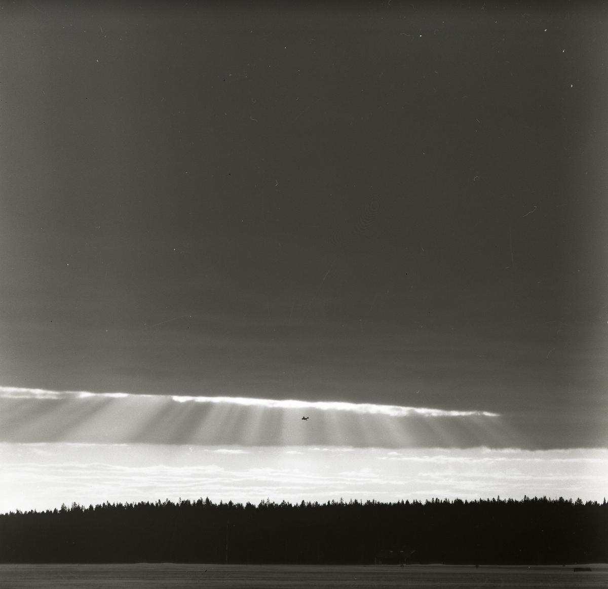 Ett flygplan av modellen J29 Tunnan flyger ovanför skog vid F15 i Söderhamn 1957. Flygplanet befinner sig intill en öppning i molntäcket där solen lyser igenom.