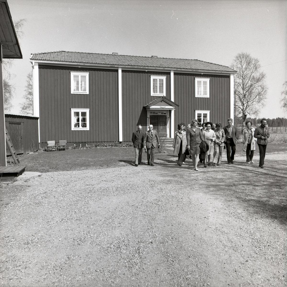 En grupp männniskor går över gårdsplanen vid gården Sunnanåker, 1974.