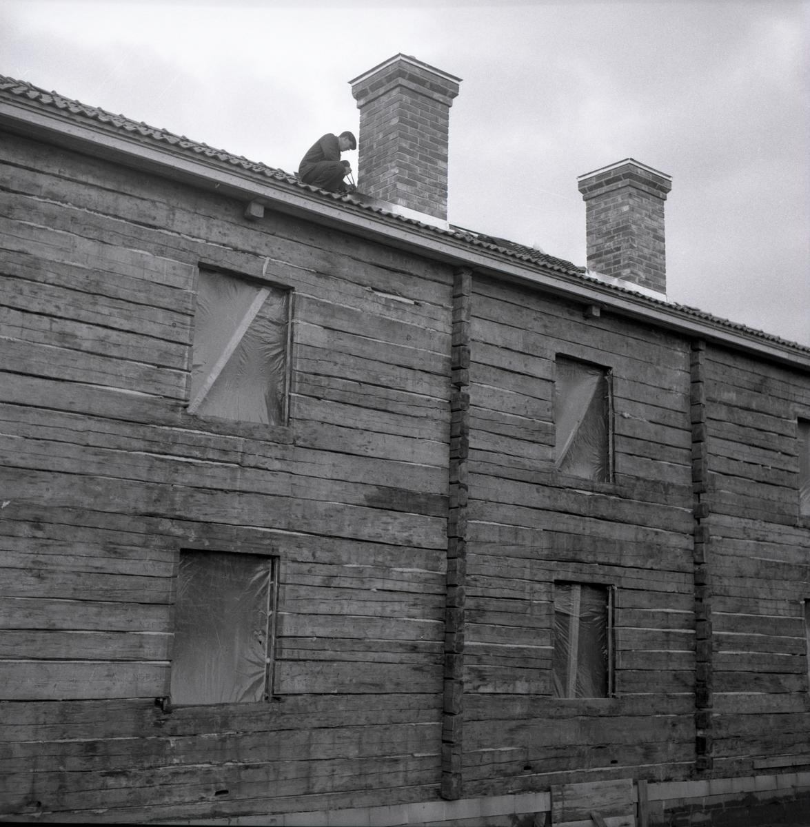 En man sitter intill en skorsten på ett tak vid gården Sunnanåker, 1967.