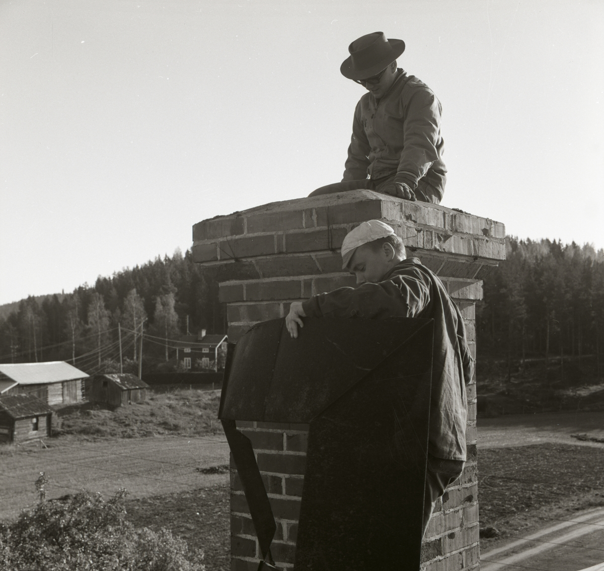Två män arbetar intill en skorsten, 1967.