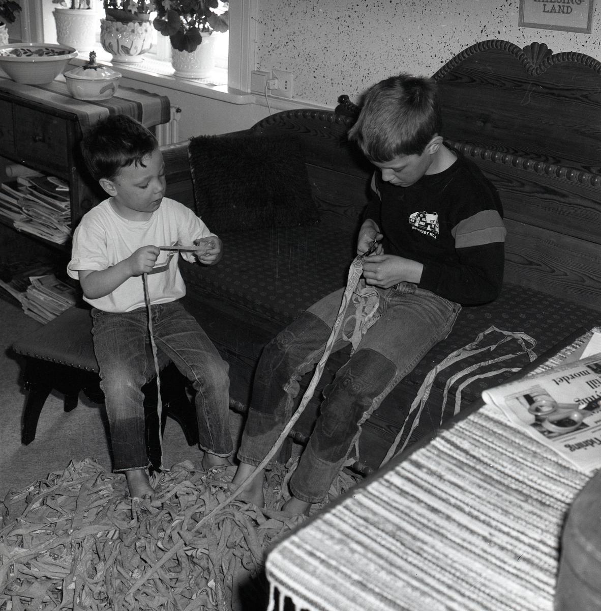 Två pojkar sitter på en träsoffa och en pall. De klipper och nystar mattrasor den 6 april 1988.