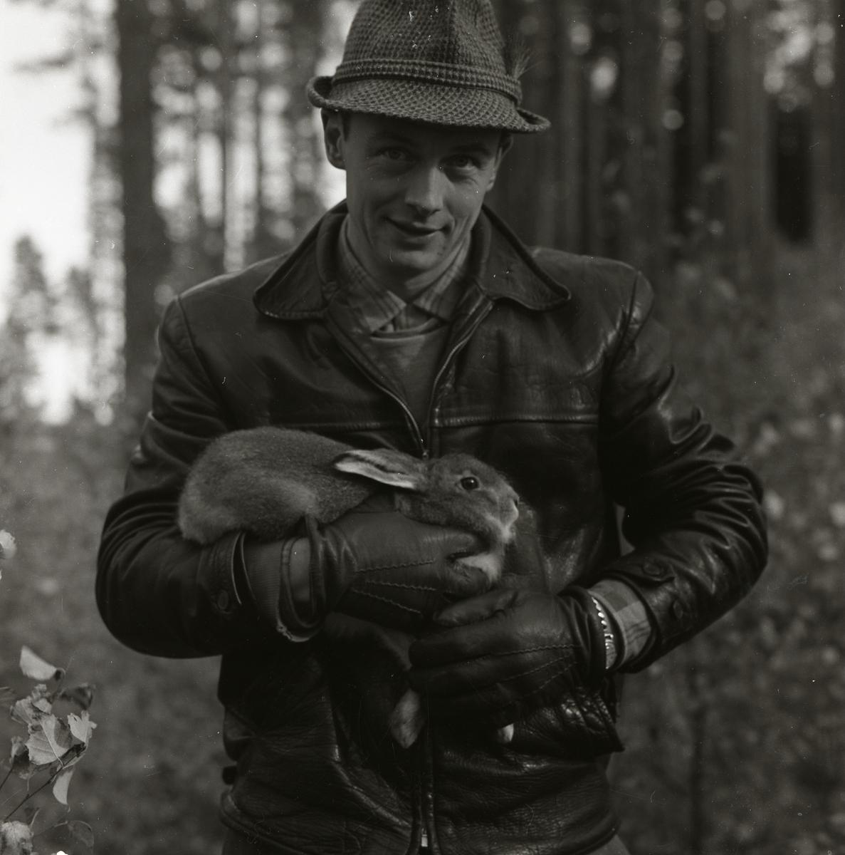 En man iförd hatt och jacka står i skogen med en hare i famnen på Storön, 6 oktober 1957.