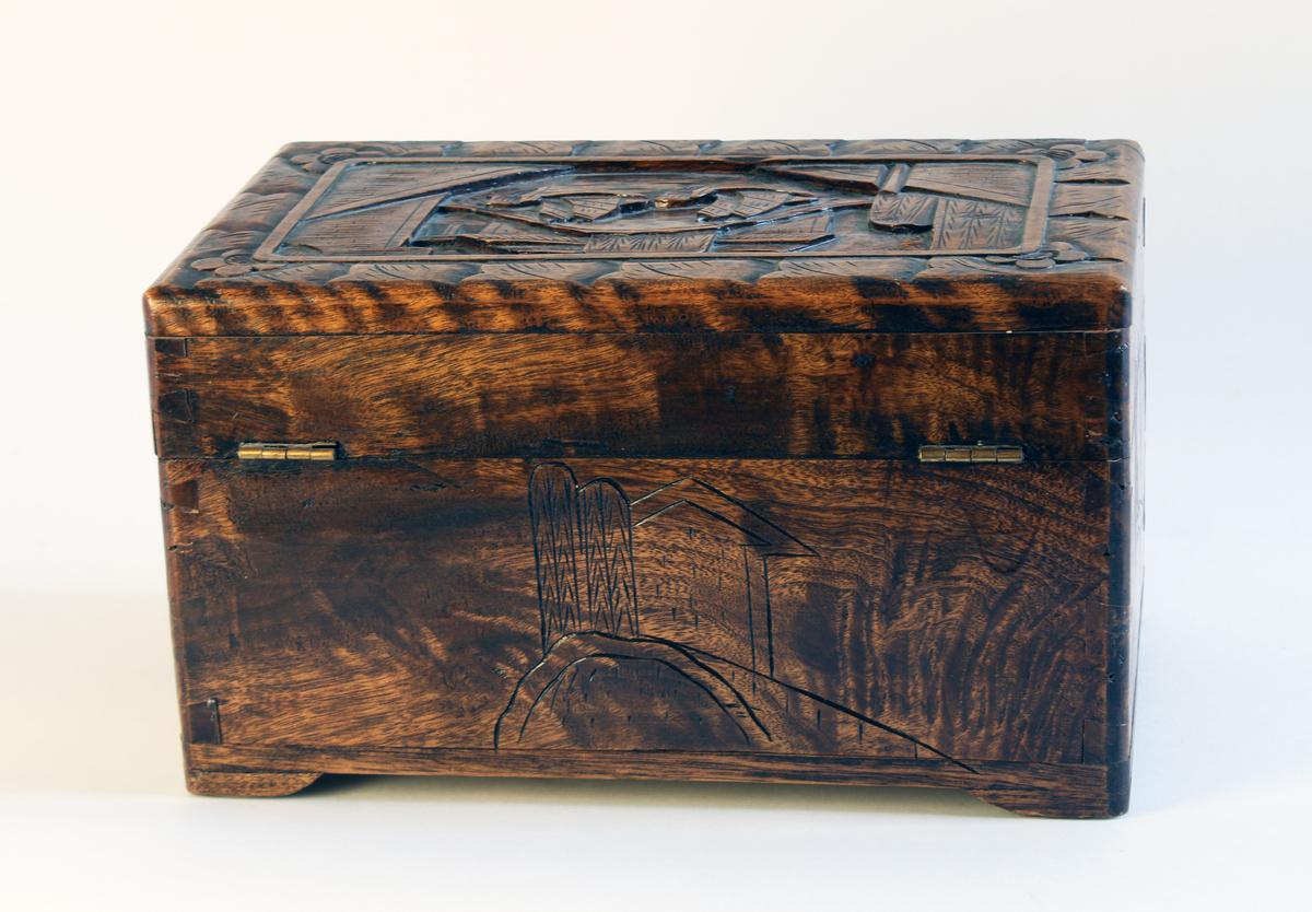 Treskrin med utskåret mønster av landskap og seilskip samt blomsterornamentikk.Hengslet med lås. Dufter godt og friskt.  For fullstendig historikk om bunad som denne gjenstanden inngår som del av, se KMR.3684.