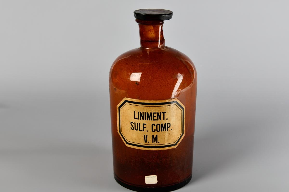 Rett flaske med hals og utkraget munning. Delvis knust glasskork sitter i munningen. Pålimt etikett der det står at flasken inneholder Liniment. Sulf. Comp. V.M.   Standkar er en beholder som ble brukt til oppbevaring av råvarer eller halvfabrikata i apotek. Det kunne være beholdere til produksjon i stor skala på laboratoriet eller mindre til den enkelte pasient i resepturen. Standkar har vært laget av tre, keramikk, metall eller glass. Apotekene hadde et stort behov for standkar, hvert apotek trengte flere hundre. Synonymer: standflaske, standglass, standbeholder, apotekkrukke og apotekglass. Fra 1960-årene gikk standkar ut av bruk. (Fra Wikipedia)
