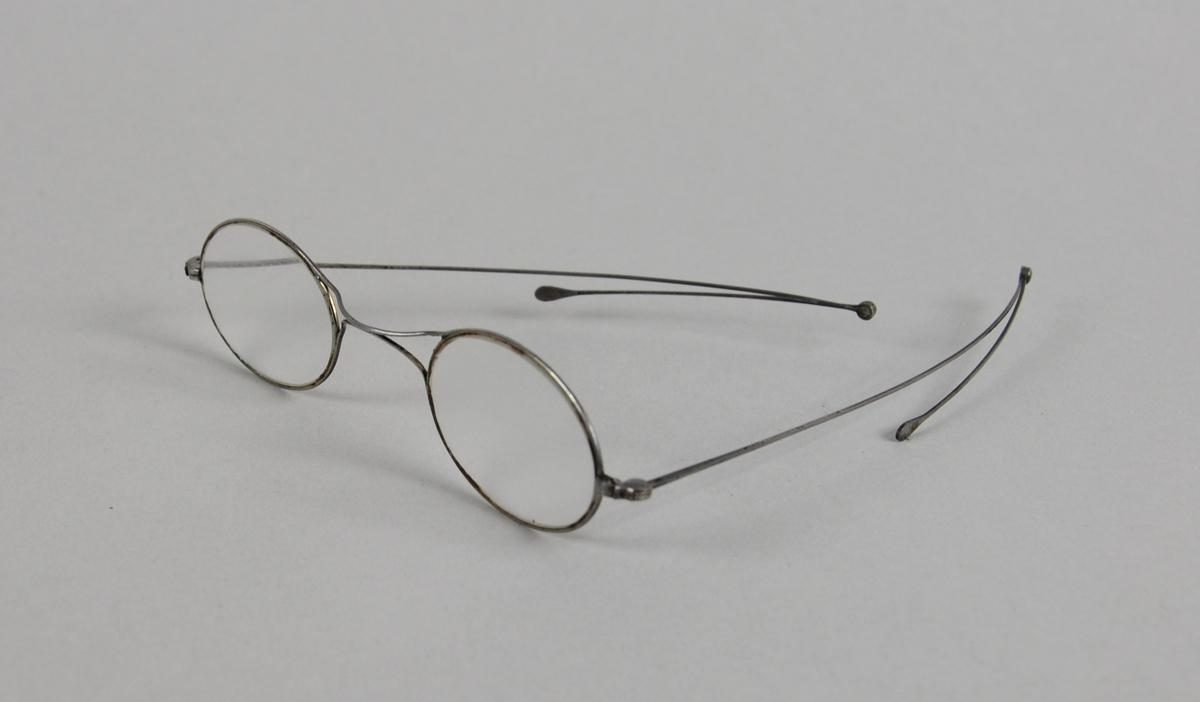 Ovale brilleglass med tynn metallinnfatning. Ytterste ledd på brillestengene kan brettes ut.