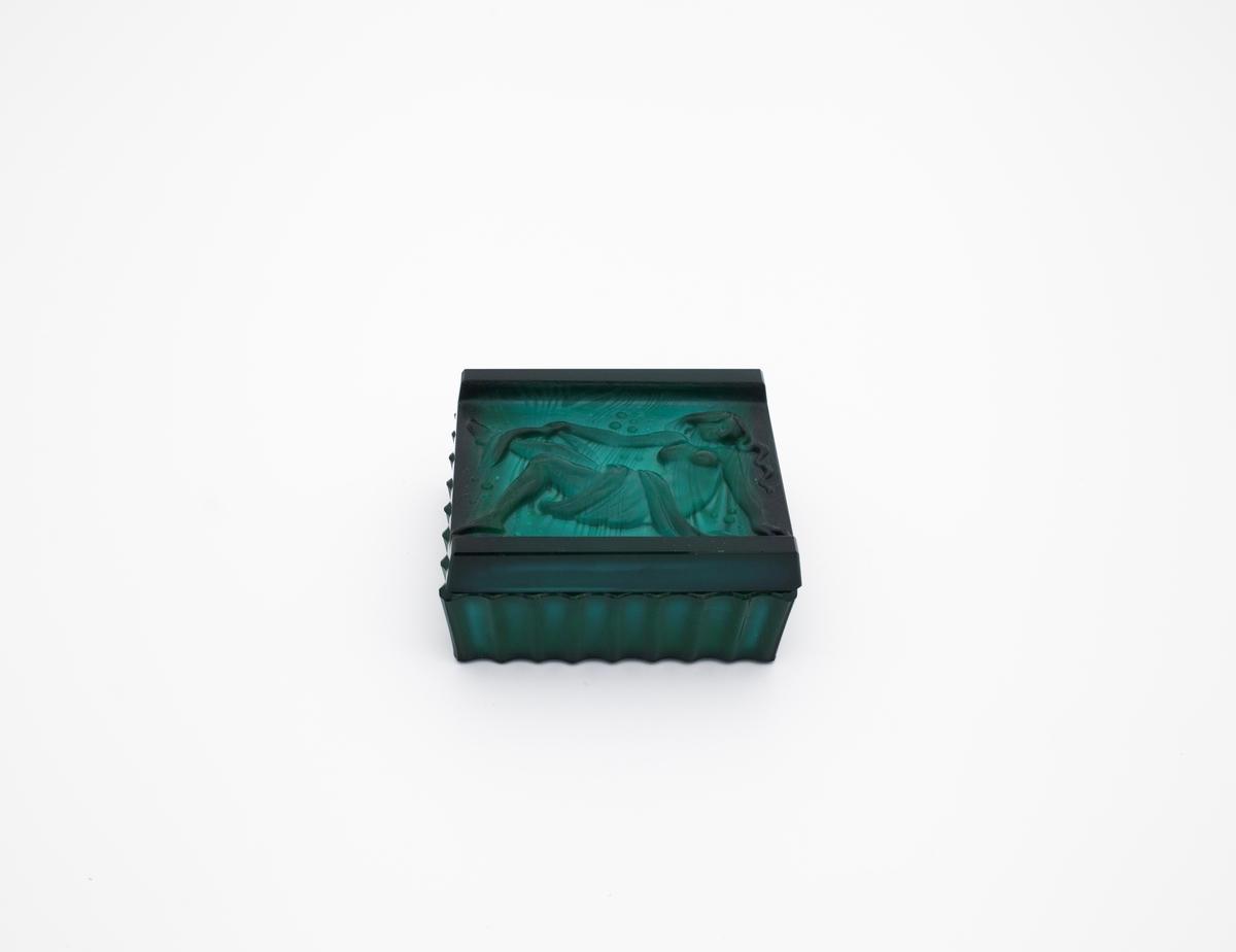 Liten boks med lokk i gjennomskinnelig glass. Lokket er dekorert med relieff av en liggende naken kvinne med et stykke tøy drapert rundt underkroppen. Boksen har riller på utsiden.