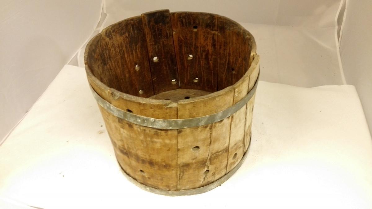 Form: Rette sider. Rund botn m/ korsforma sentrert hol. Runde hol i sider og botn. Banda m/ 2 jarnband. Ostemassen vart pakka i silklede og lagt i asken og det vart lagd press på så væta/ mysen rann gjenom hola.