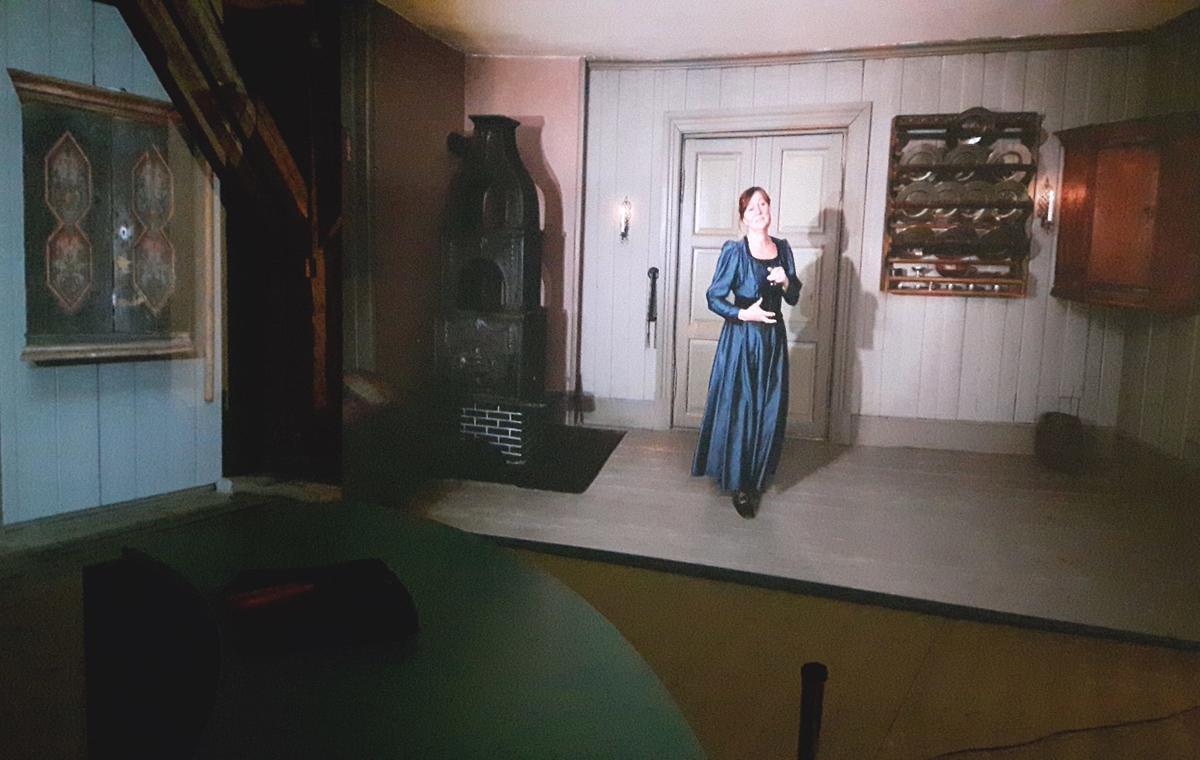 Bilde fra utstillingen BAR1567 hvor man ser en videoprojeksjon av Madam Guldberg som ønsker besøkende velkommen. (Foto/Photo)