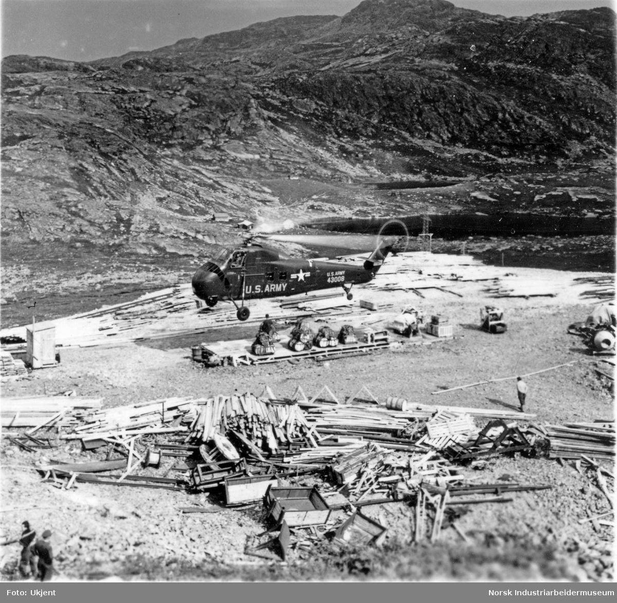 Militærhelikopter fra U.S.Army under løft for bygging av Gaustabanen. Stabler av byggematerialer ligger på frambutippen.