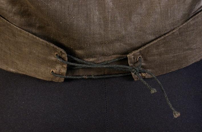 Med framstycke av svart siden, knappar trådöverklädda i violett och grönt. Vadderat bröst. Ryggstycke av svart domestik. Sleifar i ryggen med snörning. 2 rader knappar, 6 i varje, de övre dolda av slag, en knapp trasig. Från Torgilsund, Köla socken, Jösse härad.