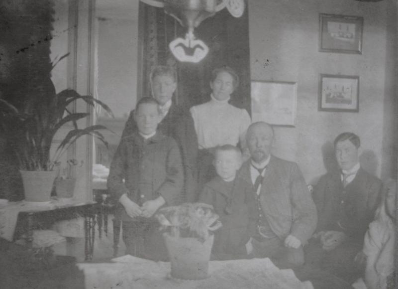Dette bildet av familien Wang er tatt i stuen på Wanggården. Foran ser vi Asbjørn, Sverre, Anders, Einar og Anne som ikke har kommet helt med på bildet. Bak ser vi Ragnvald og Karoline.
