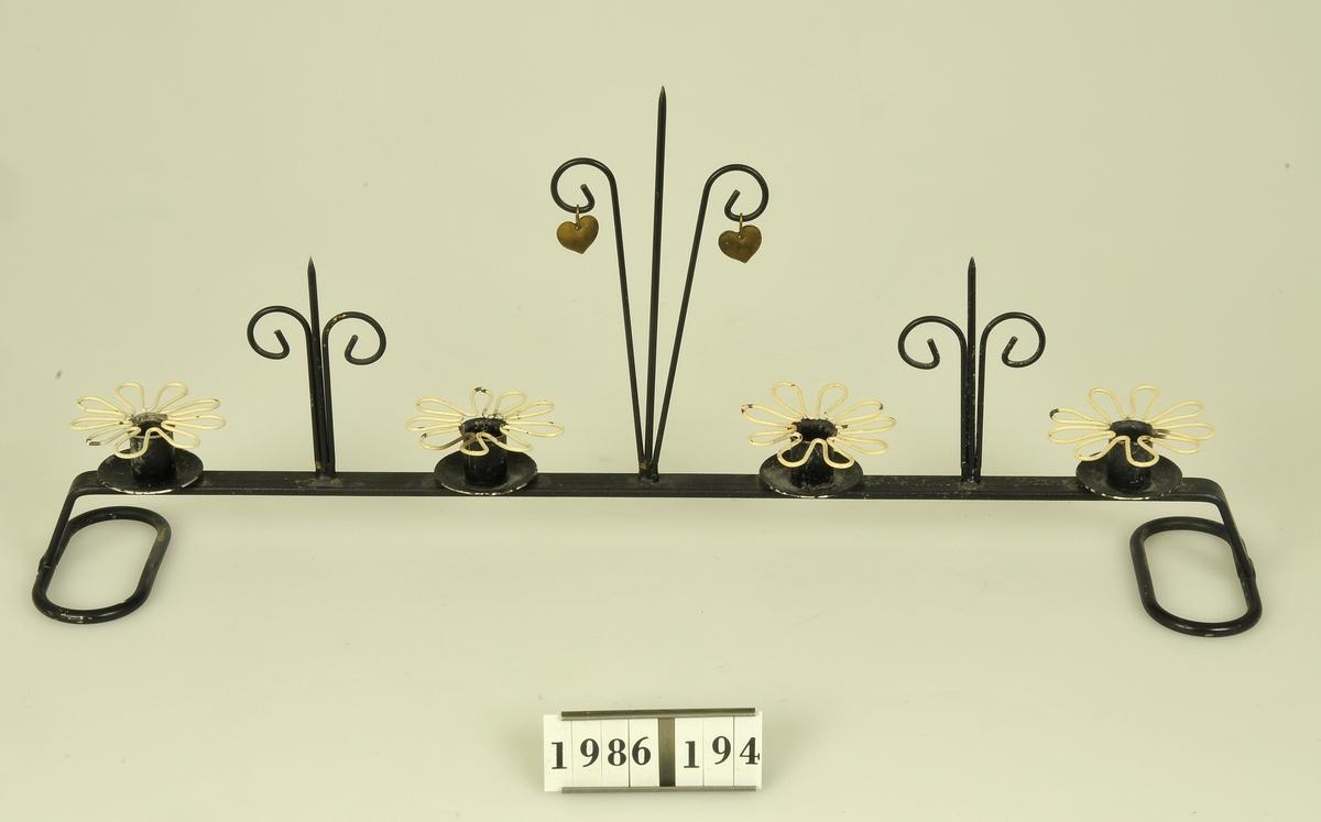 Svartlackerat. 4 st ljushållare.  Mellan hållarna dekoration av metalltråd.  Till ljusstaken hör 4 st ljusmanschetter av vitlackerad metalltråd i form av blomma.