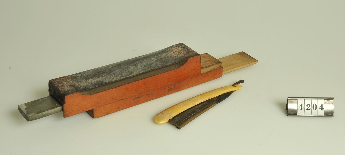 Skjutlock. Innehåller rakkniv och slipsten. På lådans undersida en strigel.  Storlek: 19,3 x 4 cm.