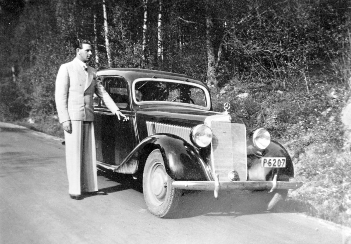 Charles Jansson, tidigare polis och senare executor, i kostym håller i dörren på en Mercedes, registreringsnummer P6207.