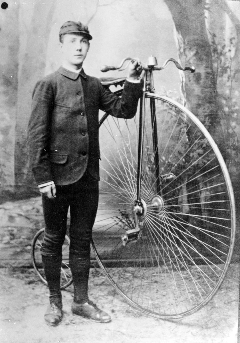 Reinhold Thorssin i knickers och mössa, fotograferad i en fotostudio, bredvid en höghjuling. Bilden är felvänd.