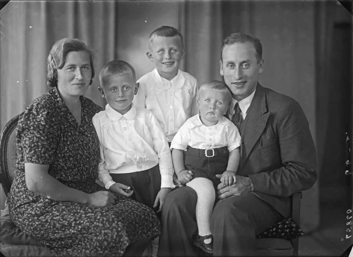 Gruppebilde. Familiegruppe på fem. Ung kvinne, tre unge gutter og ung mann. Bestilt av Reidar Reidarson. Tveita. Sveio