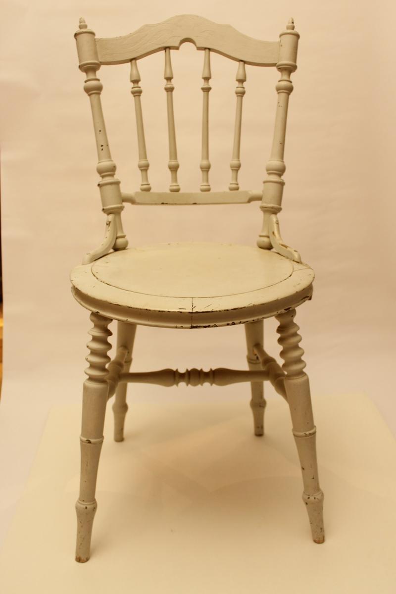Nyrenässansstol som senare är målad i ljust grått. Dekoren syns genom färgen. Ryggstycke med svarvade pinnar. Rund stolsits, svarvade ben, svarvat benkryss.
