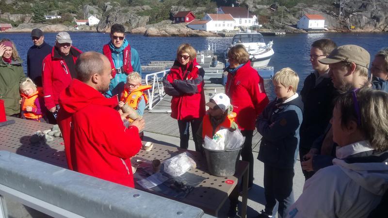Arkeolog viser frem funn fra sjøbunnen til en gruppe besøkende på brygga. (Foto/Photo)