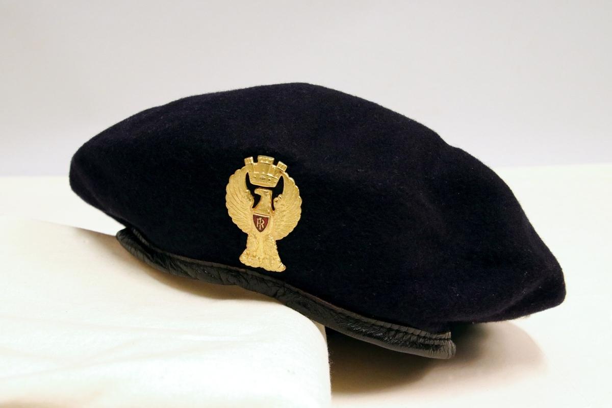 Mørk blå politiberet med luemerke med ørn i gull.