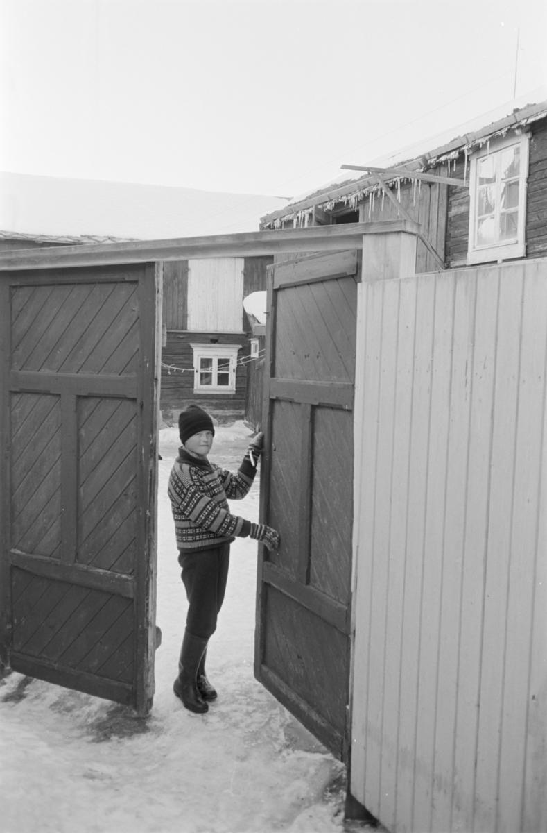 Et barn står i en port på Røros.