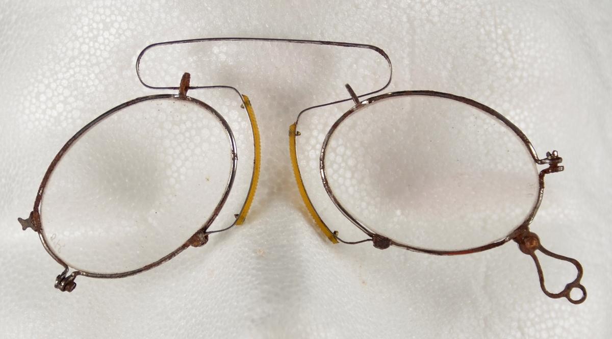 Brille. Lorgnett, Pincenez. Brille utan stenger, med naseklype. Stålinnfatta, ovale glas, stål naseklype som inn mot nasa er påsett gummi. Nede på eine sida ei hempe med hol til snor. Snor borte.