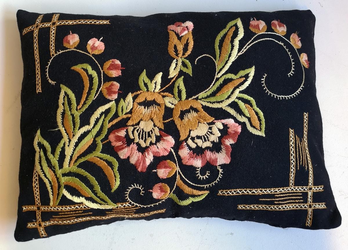 Rektanguler sofapute med stilisert blomsterbroderi.